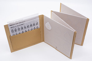 Image description: The open accordion book showing three information sheets printed on vellum tucked in a pocket. The other pages have embossed vellum slips with designated spots for the teardrop shapes to stay in. A line is embossed underneath to write out the Braille translation in English text.